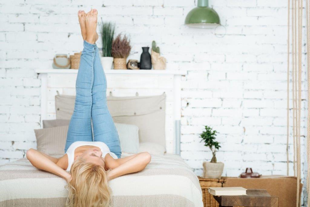kobieta leżąca na łóżku z wyciągniętymi nogami do góry