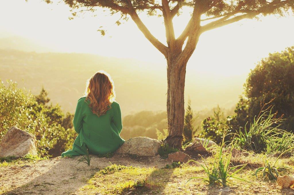 zdjęcie kobiety siedzącej przy zachodzie słońca